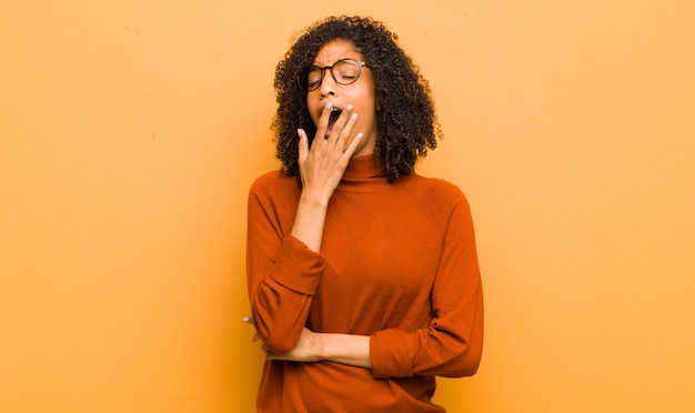 Young pretty black woman yawning lazily early in the morning, waking and looking sleepy, tired and bored against orange wall