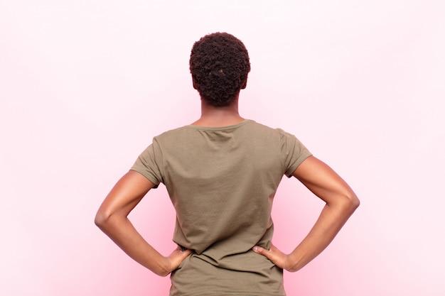 Молодая симпатичная темнокожая женщина, чувствуя себя растерянной или полной или сомневающейся и задающейся вопросом, с руками на бедрах, вид сзади на розовой стене