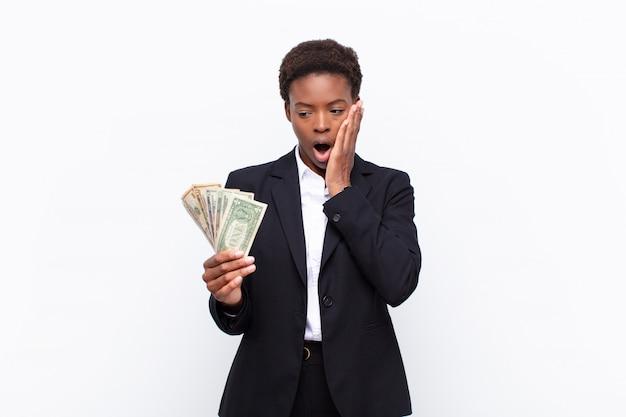Молодая симпатичная черная женщина чувствует себя потрясенной и испуганной, выглядит испуганной с открытым ртом и руками на щеках с долларовыми банкнотами