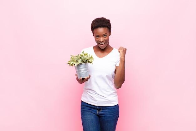Молодая симпатичная темнокожая женщина чувствует себя потрясенной, взволнованной и счастливой, смеется и празднует успех, говоря: «вау!» держать растение