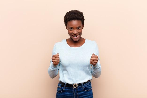 Молодая симпатичная темнокожая женщина чувствует себя потрясенной, взволнованной и счастливой, смеется и празднует успех, говоря: «вау!»