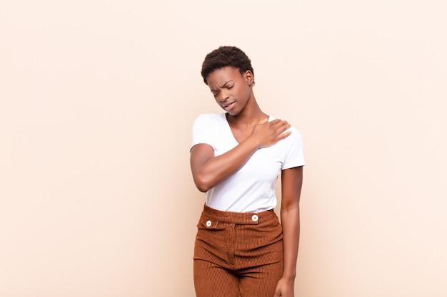 疲れ、ストレス、不安、イライラ、落ち込んで、背中や首の痛みに苦しんでいる若いかなり黒人の女性