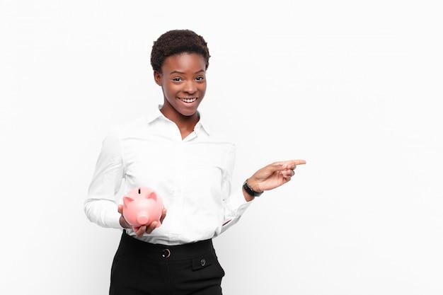 貯金箱を保持しているスペースをコピーするために側面と上向きに興奮して驚いた若いかなり黒人女性