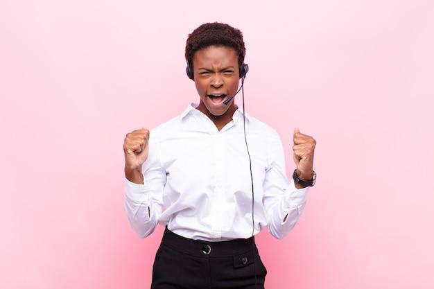 怒っている表情や拳で握りしめられて成功を祝って積極的に叫んでいる若いかなり黒人女性