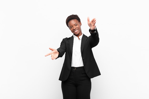 Young pretty black womansmiling cheerfully giving a warm, friendly, loving welcome hug, feeling happy and adorable against white wall