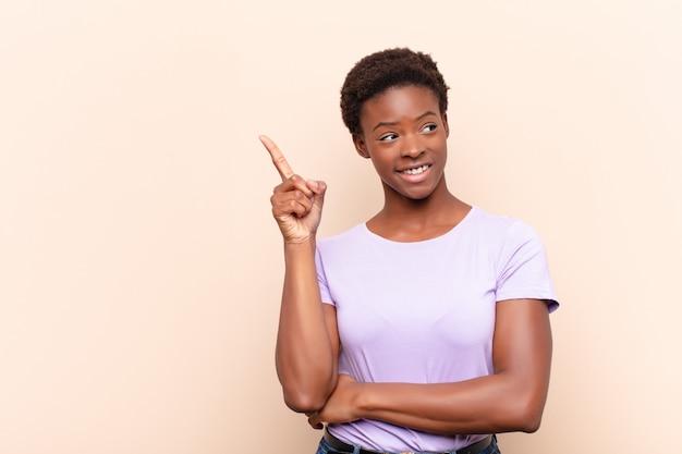 若い可愛い黒人女性の幸せそうに笑って横を向いて、不思議に思っている、考えている、またはアイデアを持っている