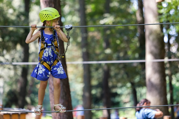 Young pretty blond child girl on rope way
