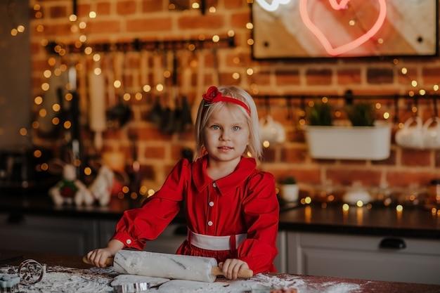 クリスマスの背景を持つキッチンで調理する赤い冬のドレスの若いきれいなブロンドの女の子