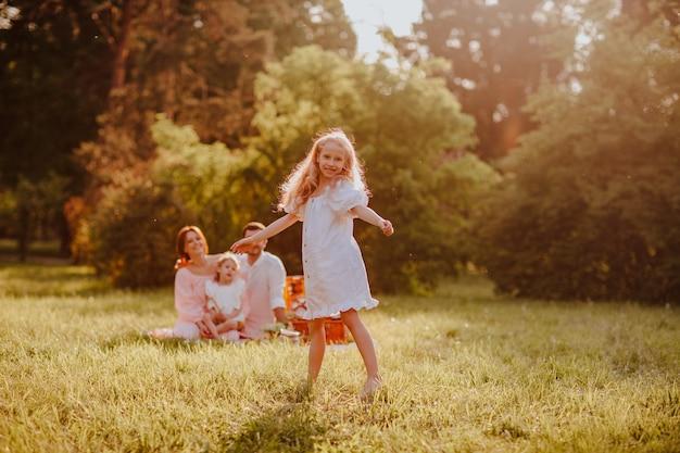 公園でポーズをとって白い夏のドレスを着た若いかわいいブロンドの女の子。