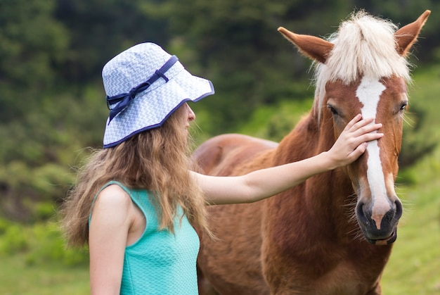 Young pretty blond long-haired woman in sun hat caressing beautiful chestnut horse on blurred green sunny summer . love to animal, care, friendship, faithfulness and farming concept.