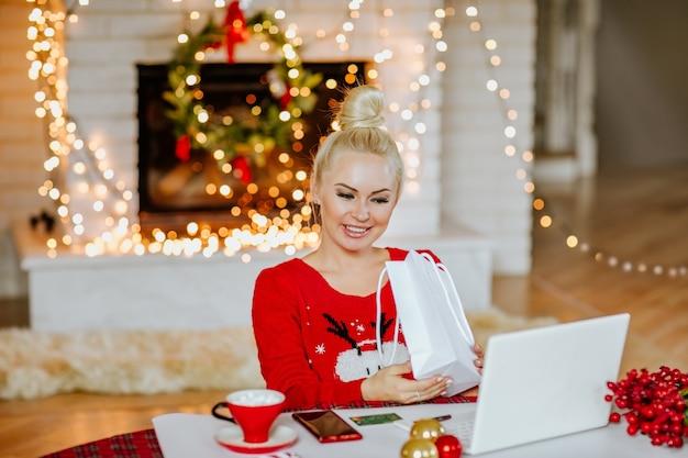 Молодая красивая белокурая женщина в красном зимнем свитере, держащем белый подарочный пакет.