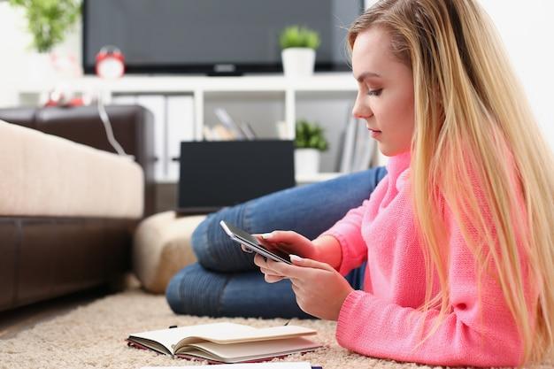 Молодая красивая блондинка женщина сидит на диване, держа в руках смартфон