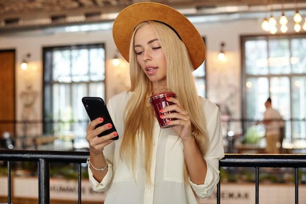 Молодая симпатичная блондинка в белой рубашке и широкой шляпе пьет лимонад во время обеденного перерыва, держит в руке мобильный телефон и смотрит на экран со спокойным лицом