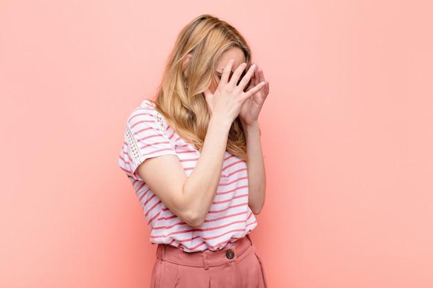 Молодая симпатичная блондинка закрыла глаза руками с грустным, разочарованным взглядом отчаяния, плача, вид сбоку на плоской цветной стене