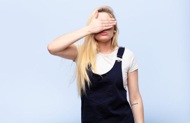 Молодая симпатичная блондинка закрыла глаза одной рукой, чувствуя испуг или беспокойство, недоумевая или слепо ожидая сюрприза у плоской стены