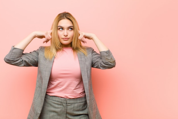 Young pretty blonde woman feeling confused or doubting, concentrating on an idea, thinking hard, looking to copy space on side against flat wall