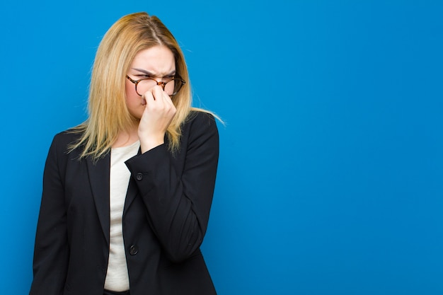 Young pretty blonde woman feeling disgusted, holding nose to avoid smelling a foul and unpleasant stench against flat wall