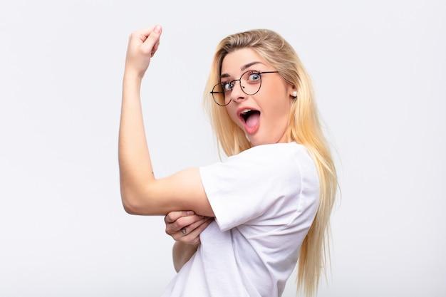 若いかなりブロンドの女性は幸せ、満足、強力な感じ、柔軟なフィット感、上腕二頭筋、白い壁にジムを強く見た後
