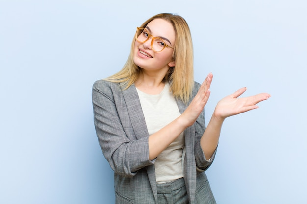 Young pretty blonde woman feeling happy and successful, smiling and clapping hands