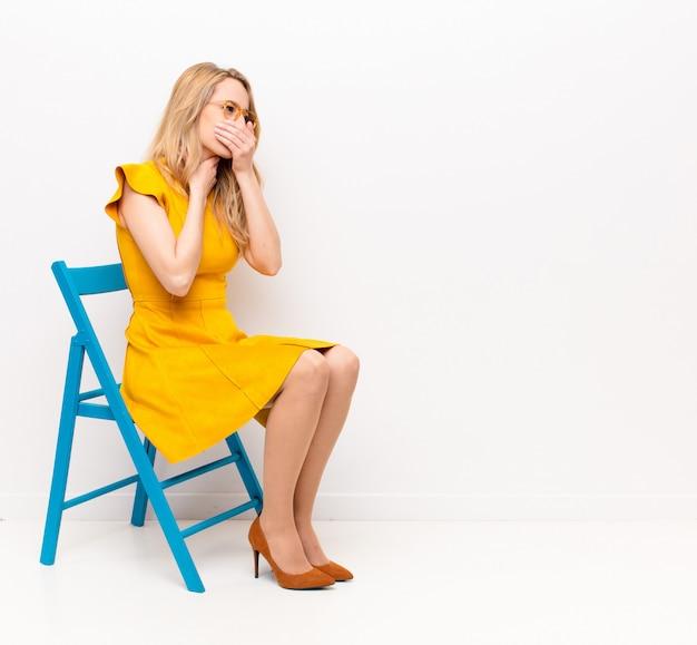 Молодая симпатичная блондинка чувствует себя плохо, с симптомами гриппа и болью в горле, кашляет, прикрыв ртом плоскую цветную стену