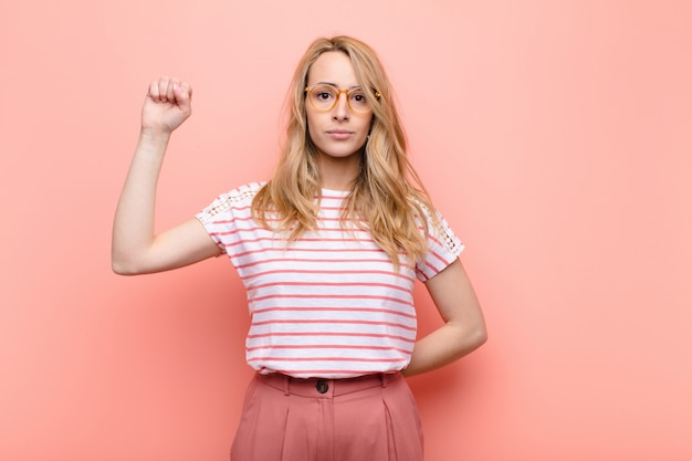Young pretty blonde woman feeling serious, strong and rebellious, raising fist up, protesting or fighting for revolution against flat color wall
