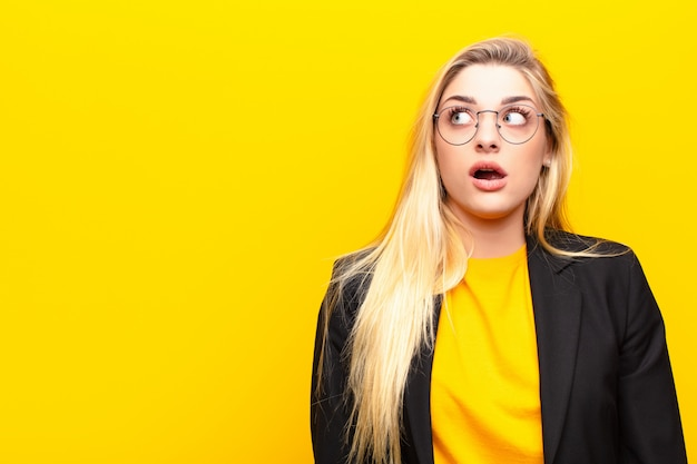 Young pretty blonde woman feeling shocked, happy, amazed and surprised, looking to the side with open mouth over yellow wall