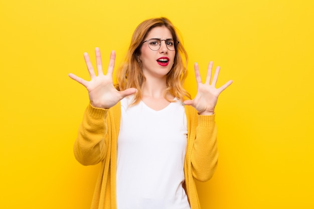 Young pretty blonde woman feeling stupefied and scared, fearing something frightening, with hands open up front saying stay away against yellow wall