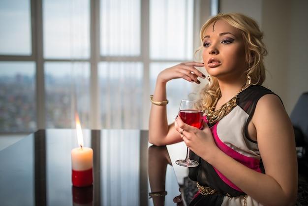 보석에 젊은 예쁜 금발의 여자는 불타는 촛불 테이블에 앉아서 도시 파노라마와 함께 큰 창의 배경에 주스 또는 와인을 마신다. 날짜를 기다리는 개념