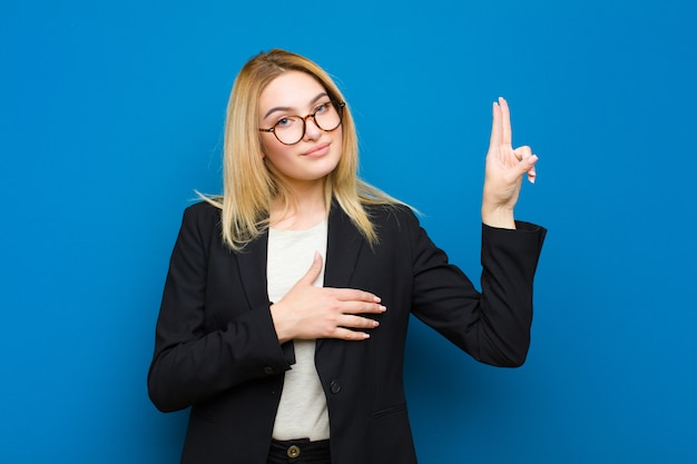 Young pretty blonde woman looking happy, confident and trustworthy, smiling and showing victory sign, with a positive attitude against flat wall