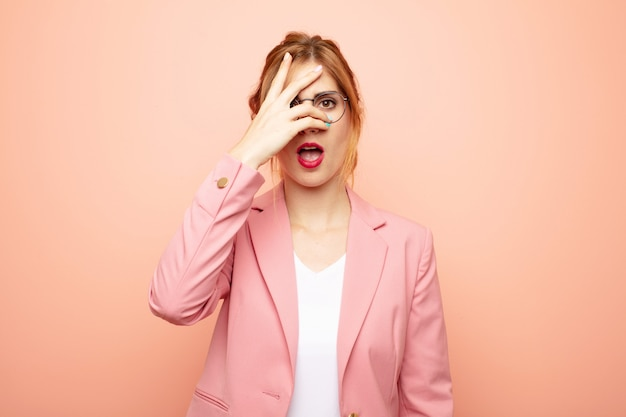 Young pretty blonde woman looking shocked, scared or terrified, covering face with hand and peeking between fingers. business concept