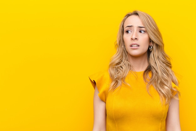 Young pretty blonde woman looking worried, stressed, anxious and scared, panicking and clenching teeth against flat color wall