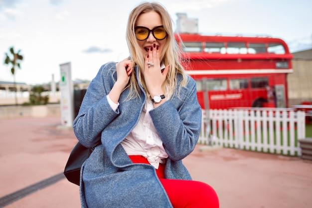 Молодая симпатичная блондинка позирует на улице, в модном пальто и рюкзаке, студенческом стиле битник, весело и улыбаясь, милое позитивное лицо.
