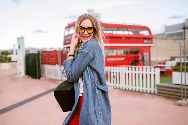 Giovane bella donna bionda in posa per strada, indossando cappotto e zaino alla moda, stile studente hipster, divertendosi e sorridente, viso positivo carino.