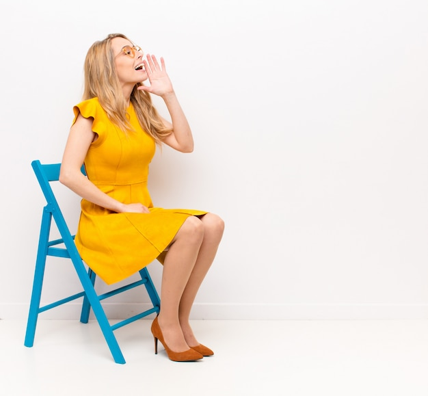 Young pretty blonde woman profile view, looking happy and excited, shouting and calling to copy space on the side against flat color wall