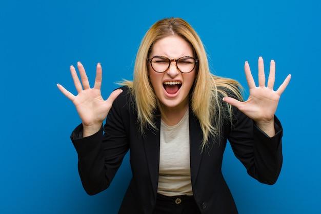 パニックや怒り、ショックを受けた、恐怖または激怒で叫んで、平らな壁に頭の横にある手で若いかなりブロンドの女性