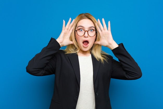 Young pretty blonde woman screaming with hands up in the air, feeling furious, frustrated, stressed and upset against flat wall