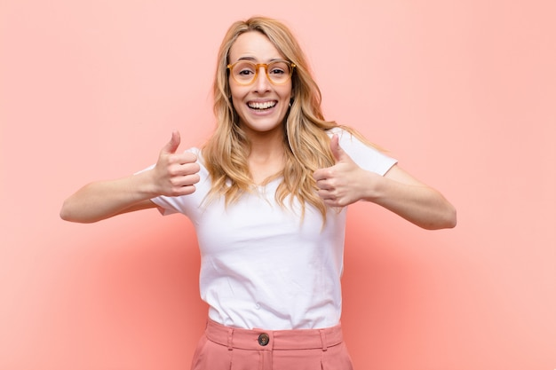 Young pretty blonde woman smiling broadly looking happy, positive, confident and successful, with both thumbs up against flat color wall