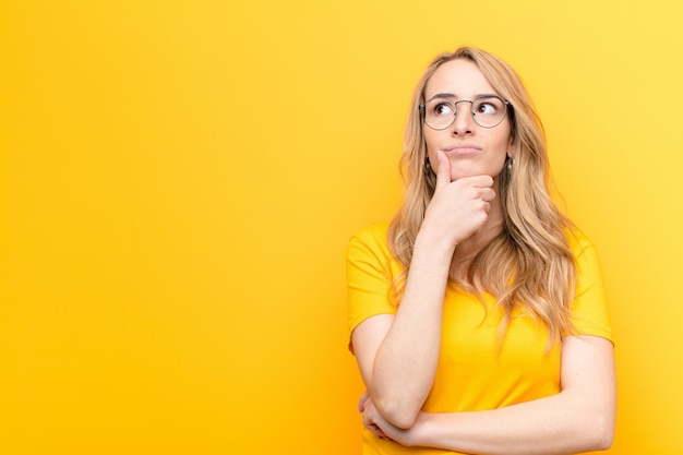 Молодая симпатичная белокурая женщина думает, чувствует себя сомнительно и растерянно, с разными вариантами, гадая, какое решение сделать на фоне цветной стены