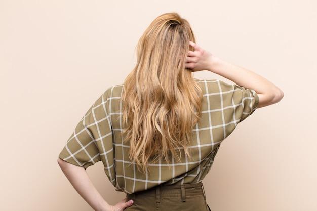 Молодая симпатичная блондинка думает или сомневается, почесывает голову, чувствует недоумение и замешательство, вид сзади или сзади на плоской цветной стене