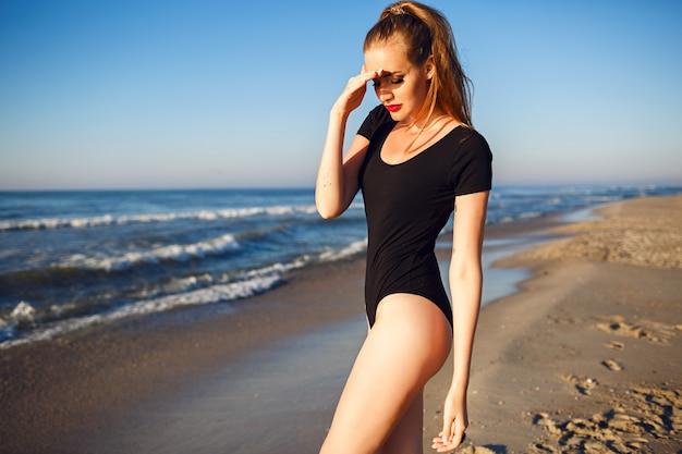 Giovane bella donna bionda che indossa un bikini nero, corpo snello, godersi le vacanze e divertirsi sulla spiaggia, lunghi capelli biondi, occhiali da sole e cappello di paglia. da solo vicino all'oceano