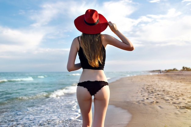 Young pretty blonde woman wearing black bikini, slim body, enjoy vacation and having fun on the beach, long blonde hairs, sunglasses and straw hat. vacation on bali.