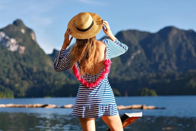 Giovane bella donna bionda con i capelli lunghi, che indossa un cappello vintage e vestito alla moda sexy luminoso guarda alle montagne e al lago, mostra la sua mano, incredibili avventure estive.