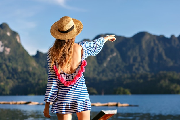 Young pretty blonde woman with long hairs, wearing vintage hat and bright sexy trendy dress looks to the mountains and lake, show her hand, amazing summer adventures.
