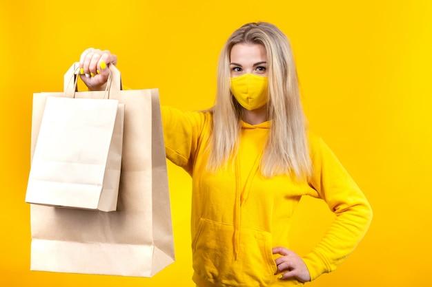 黄色の防護マスクの紙エコバッグを持つ若いかなりブロンドの女性