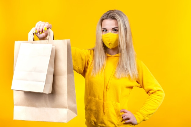 Young pretty blonde woman with paper eco-bag in yellow protective mask