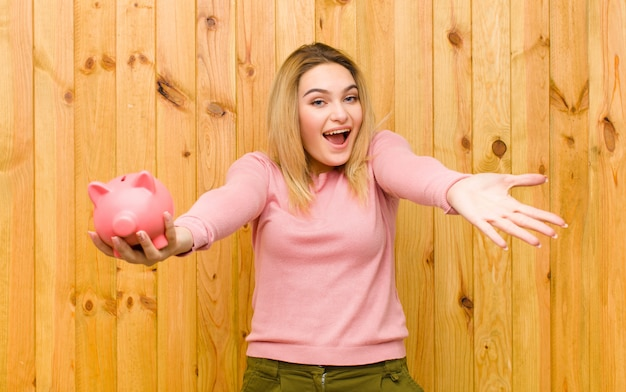 Young pretty blonde woman with a piggy bank  wood wall