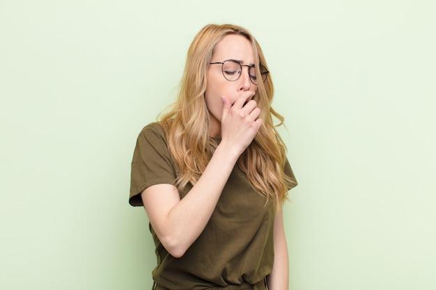 Молодая симпатичная блондинка лениво зевает рано утром, просыпается и выглядит сонной, уставшей и скучающей на фоне плоской цветной стены