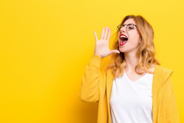 Young pretty blonde woman yelling loudly and angrily on the side, with hand next to mouth over yellow wall