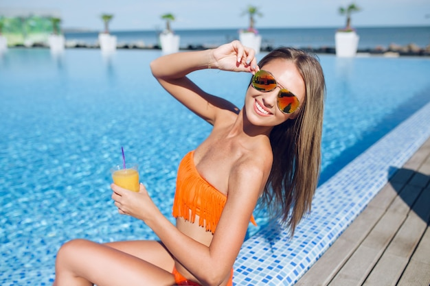 Young pretty blonf girl with long hair is sitting near pool on sun. she holds cocktail and smiling to the camera.