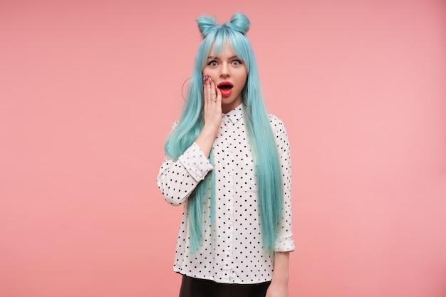 Giovane donna dai capelli blu piuttosto con labbra rosa che guarda sorpreso e tenendo il palmo sulla guancia
